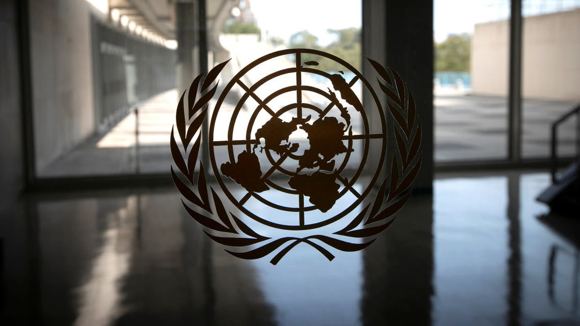 The UN logo is seen on a window in an empty hallway at United Nations headquarters, Sept. 21, 2020. (Reuters)