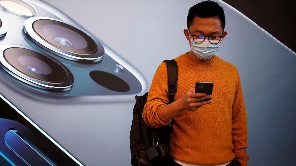 A man wears a face mask while waiting at an Apple Store before Apple's 5G new iPhone 12 go on sale. (Reuters)