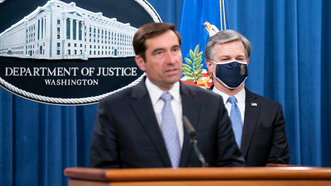 Assistant Attorney General for National Security John C. Demers, left, and FBI Director Christopher Wray participate in a virtual news conference at the Department of Justice on October 28, 2020 in Washington, DC. Eight people have been arrested as part of Operation Fox Hunt, an effort by the People's Republic of China to threaten people to return to the country. (Photo by Sarah Silbiger/Getty Images)