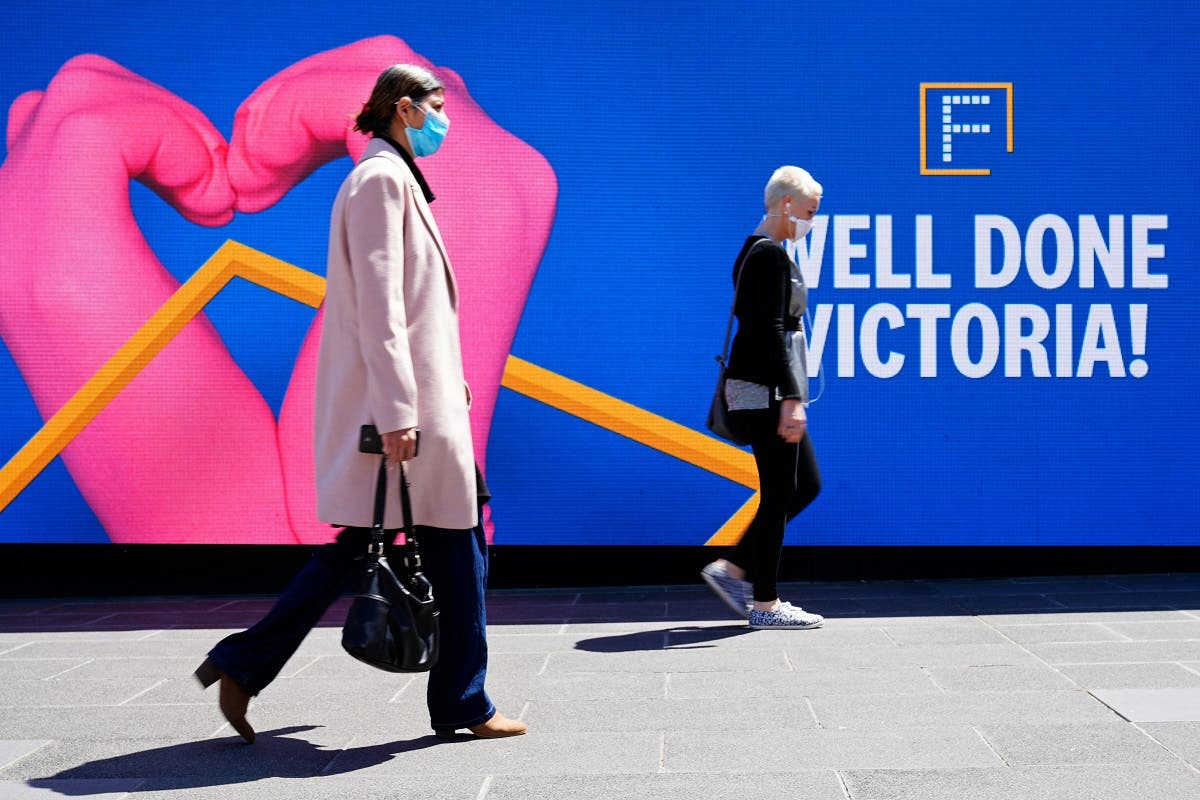 People walk past a 'Well Done' sign after coronavirus restrictions were eased for the state of Victoria, in Melbourne, Australia, on October 28, 2020. (Reuters)