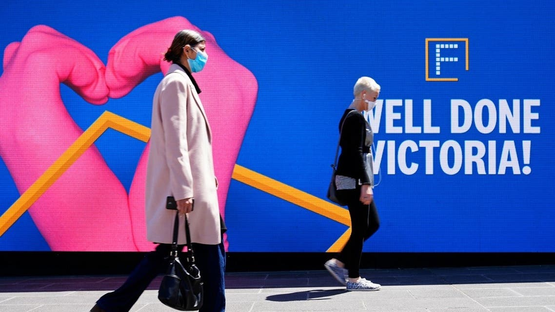 People walk past a 'Well Done' sign after coronavirus restrictions were eased for the state of Victoria, in Melbourne, Australia, October 28, 2020. (Reuters)