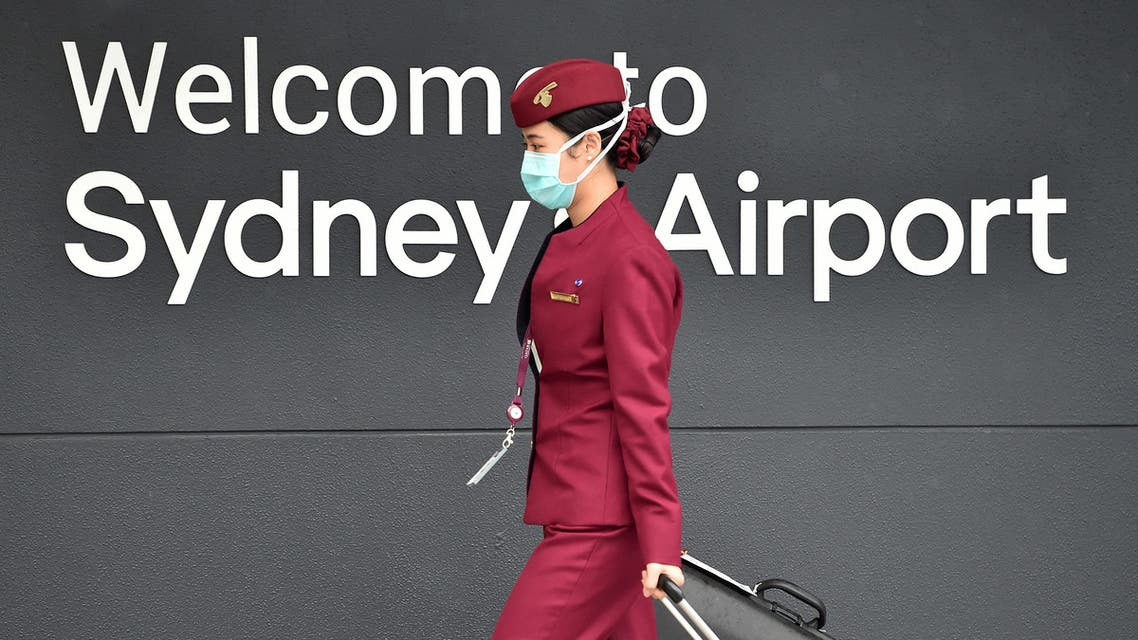(FILES) In this file photo taken on April 2, 2020, a Qatar Airways crew member enters Sydney international airport to fly on a repatriation flight back to France amid the COVID-19 coronavirus pandemic. Revelations that passengers flying through Doha were forced to endure vaginal inspections have upended Qatar's efforts to boost its reputation before the Gulf state hosts World Cup 2022, experts say. Officers marched women off a Sydney-bound Qatar Airways flight earlier this month and forced them to undergo intimate examinations after a newborn baby was found abandoned in an airport bathroom.