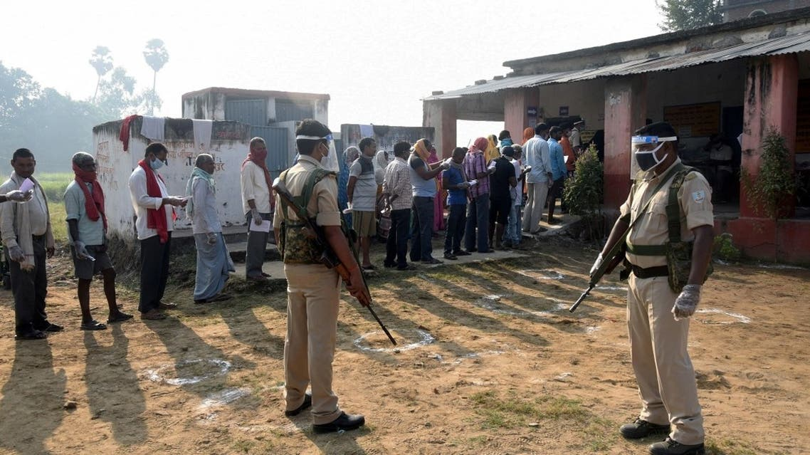 Policemen wearing protective face shields stand guard as voters stand in a queue to cast their vote outside a polling booth during the state assembly election, at a village on the outskirts of Patna, in the eastern state of Bihar, India, on October 28, 2020. (Reuters)