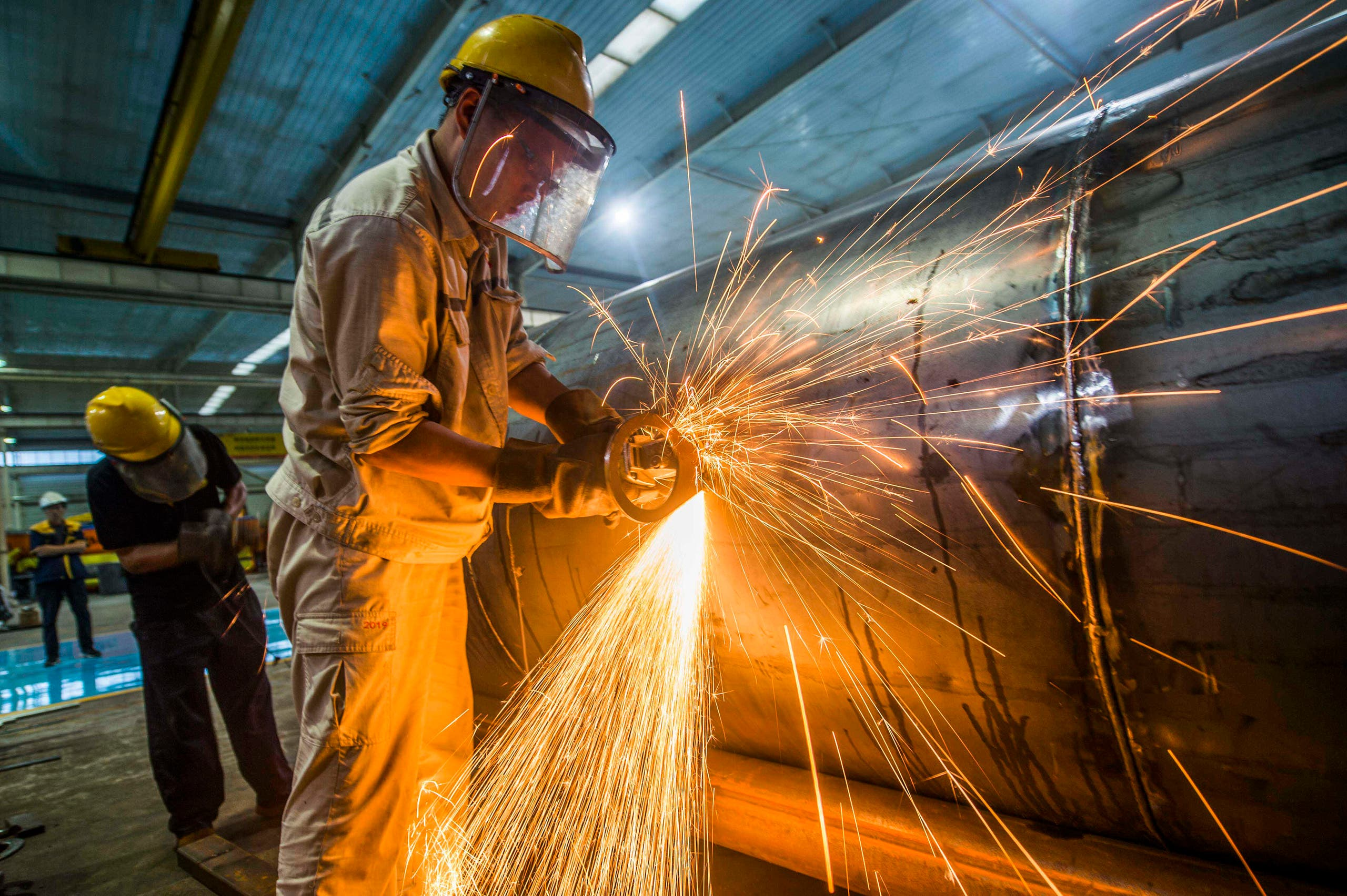 A worker welds medal truck parts at a factory in Weifang in China's eastern Shandong province on August 14, 2020. (AFP)