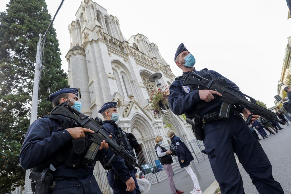 Police officers stand guard by the Notre-Dame de l'Assomption Basilica in Nice on October 29, 2020. (AFP)