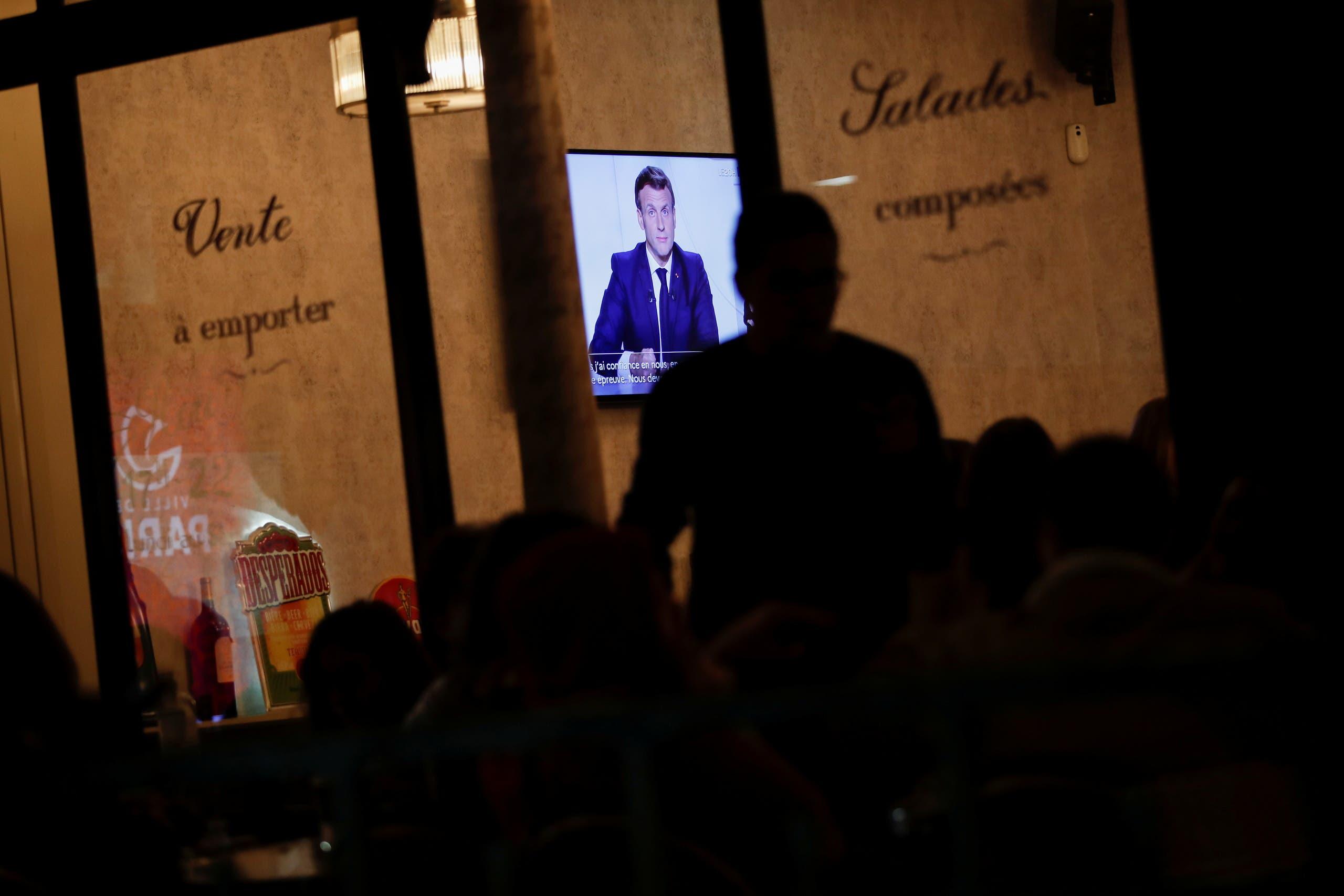 فرنسيون يستمعون إلى كلمة ماكرون في أحد مقاهي باريس قبل الإقفال