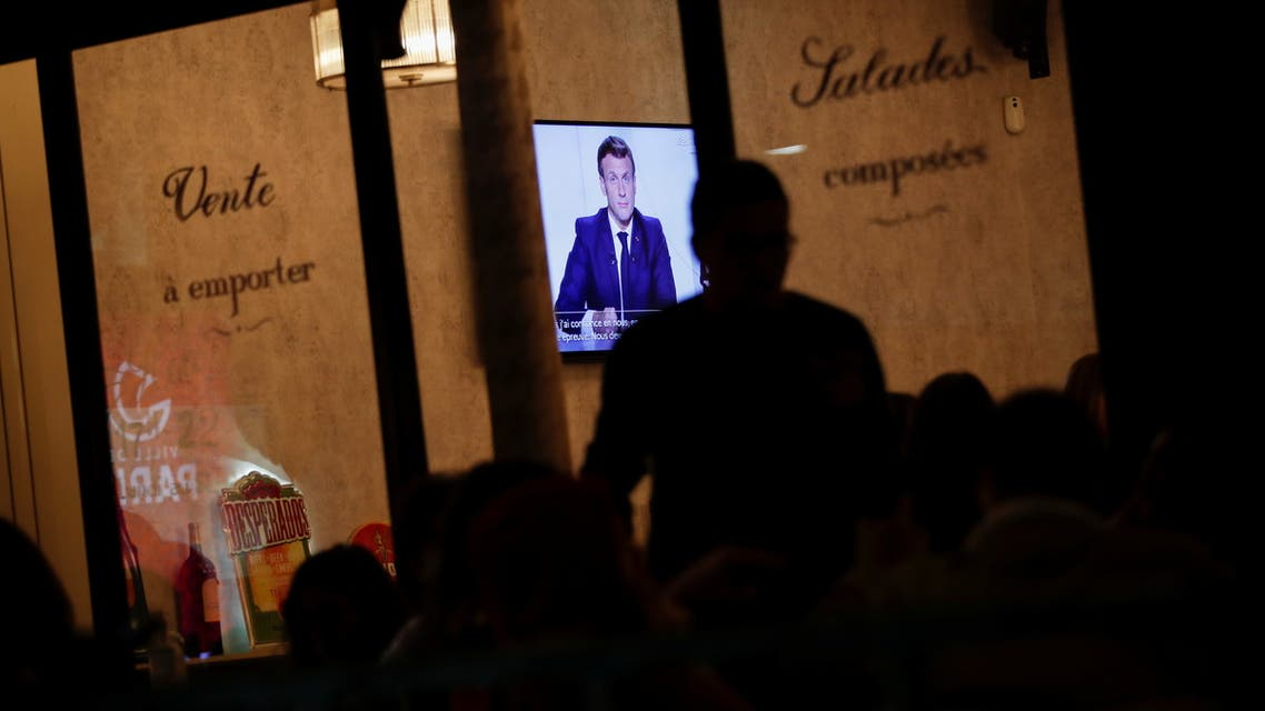 People watch French President Emmanuel Macron on a TV screen in a restaurant in Paris as the French leader addresses the nation about the state of the coronavirus disease (COVID-19) outbreak in France, October 28, 2020. REUTERS/Benoit Tessier