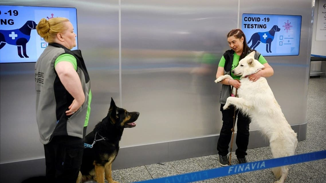 The coronavirus sniffer dogs named Valo (L) and E.T. stand by their trainers at the Helsinki airport in Vantaa, Finland, September 22, 2020. (Antti Aimo-Koivisto/Lehtikuva/AFP)