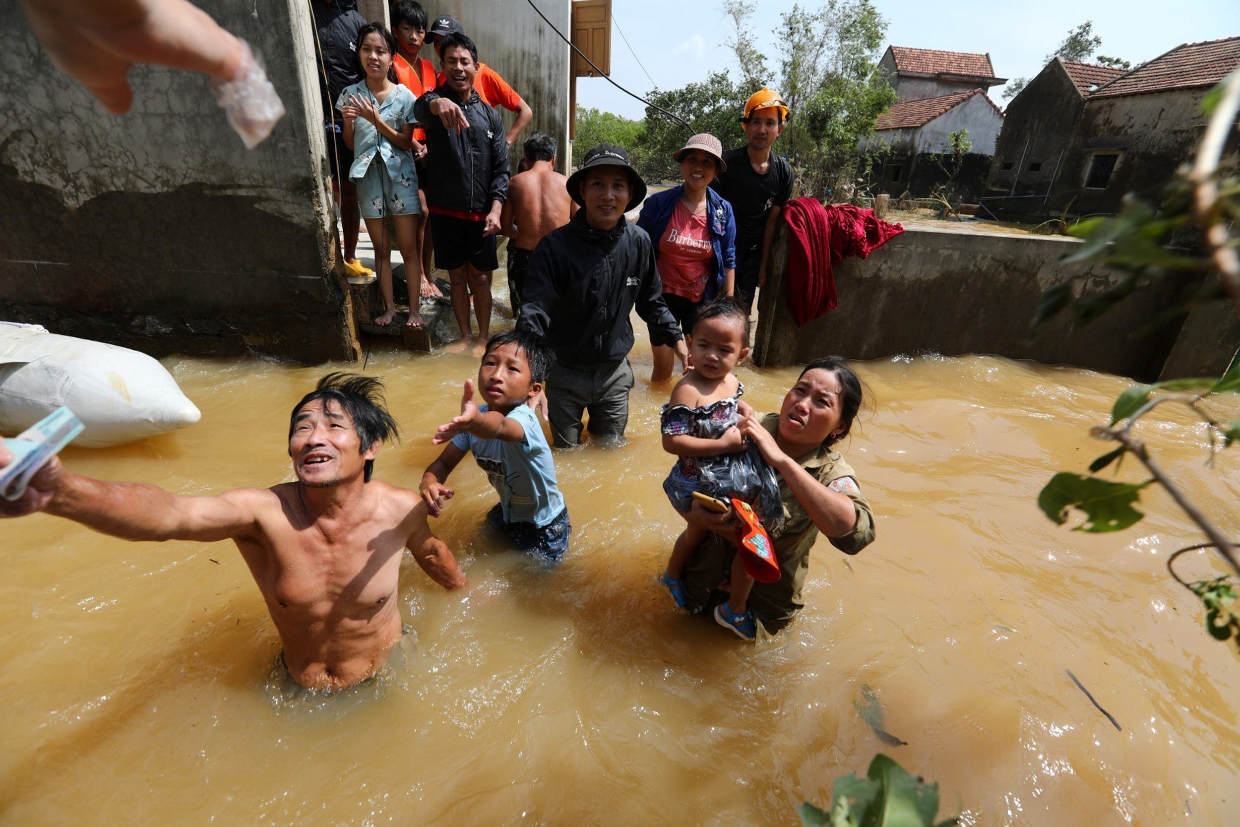 A resident gets money from a volunteer at a flooded area in Quang Binh province, Vietnam October 23, 2020. (Reuters)