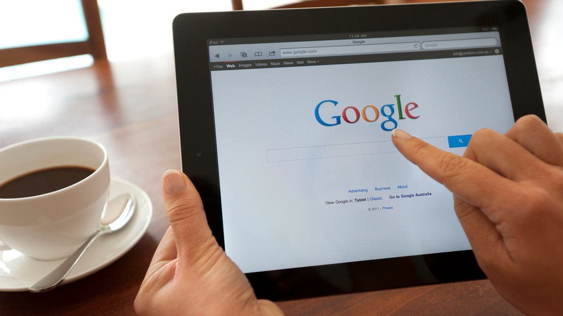 Female hand holding an ipad showing Google. stock photo Sydney, Australia - October 28, 2011: Female hand holding an ipad showing Google. She is touching the screen. There is coffee on the dining table in the background. This image shows the ipad being used in a casual environment.