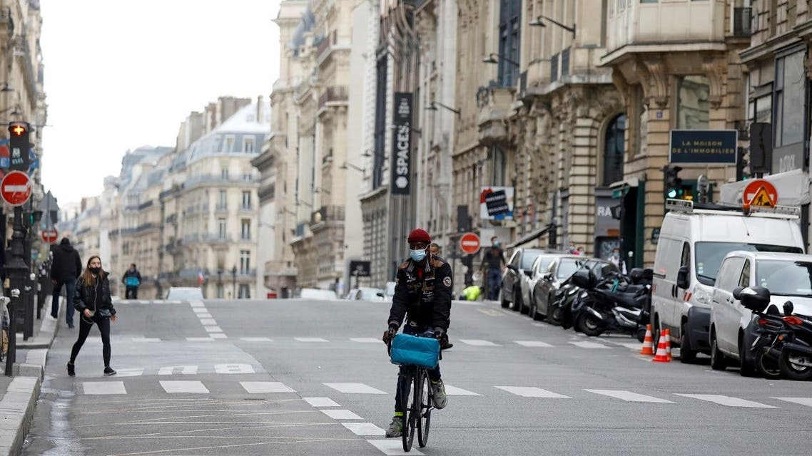 2020-10A man rides a bicycle in an almoste deserted street in Paris on the first day of the second national lockdown as part of the COVID-19 measures to fight a second wave of the coronavirus disease (COVID-19), France, October 30, 2020. (Reuters)-30T122453Z_1626020540_RC20TJ9ZO97X_RTRMADP_3_HEALTH-CORONAVIRUS-FRANCE-LOCKDOWN