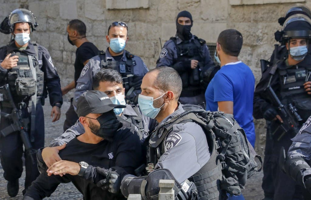 Members of the Israeli security forces restrict a Palestinian taking part in a protest against the French president, in the al-Aqsa mosque compound, in the Old City of Jerusalem on October 30, 2020. (AFP)