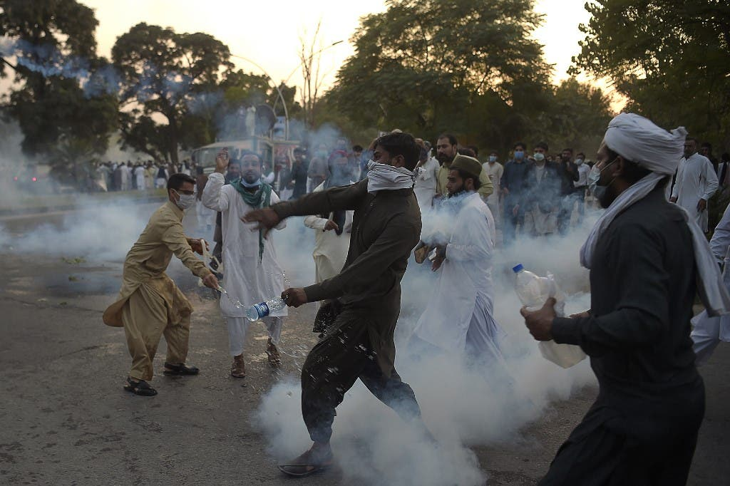 Pakistani protesters return teargas shells during a demonstration in Islamabad on October 30, 2020, following French President Emmanuel Macron's comments over the Prophet Mohammed caricatures. (AFP)