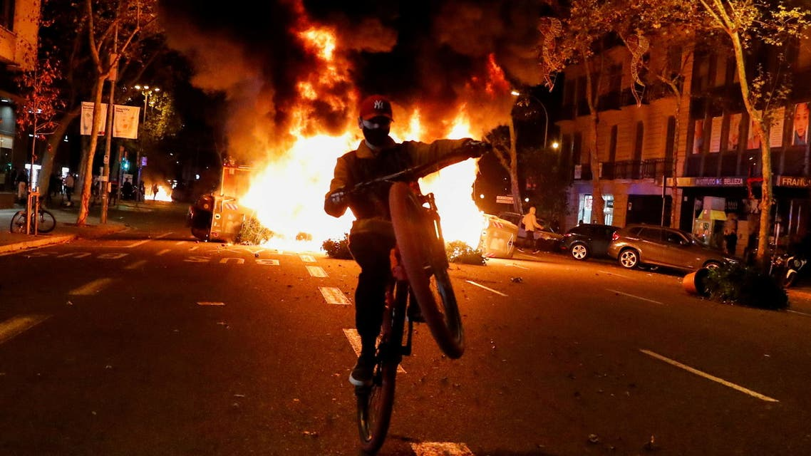 A person rides a bicycle in front of a fire during a protest against the closure of bars and gyms, amidst the coronavirus disease (COVID-19) outbreak, in Barcelona, Spain October 30, 2020. (Reuters)