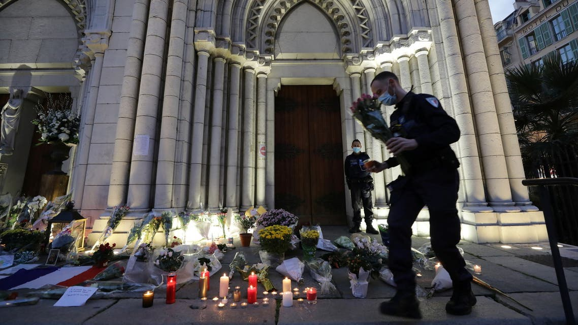 A man lights a candle near the Notre Dame church in tribute to the victims of a deadly knife attack in Nice, France, October 30, 2020. REUTERS/Eric Gaillard