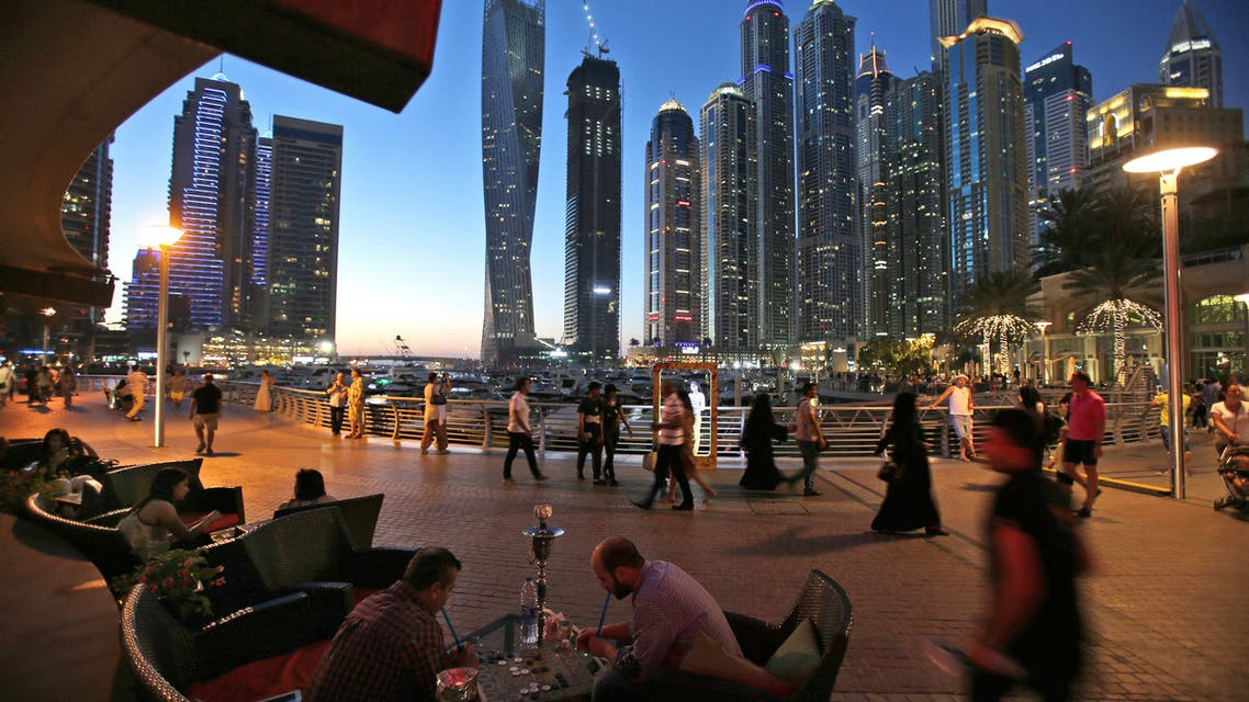 Two men play backgammon while smoking a shisha water pipe at a restaurant overlooking the canal and the Dubai Marina neighborhood in Dubai on May 1, 2015. (AP)
