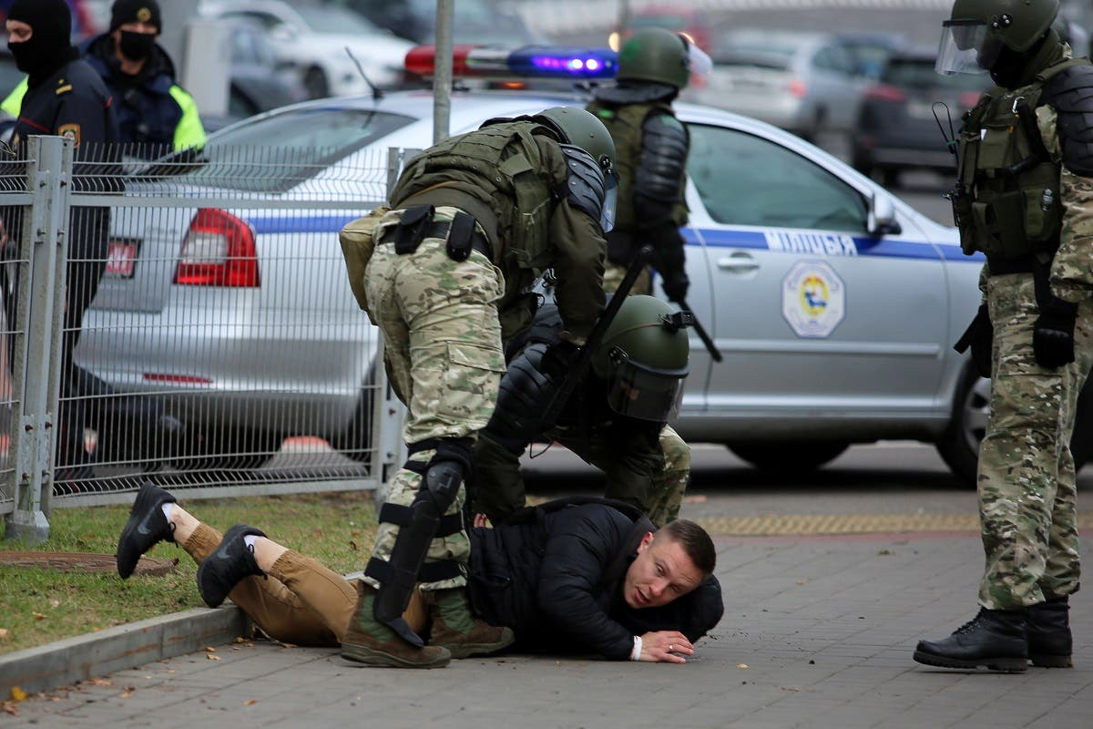 Law enforcement officers detain a man during a  march of opposition supporters from central Minsk to a site of Stalin-era executions just outside the capital on November 1, 2020. (Stringer/AFP)