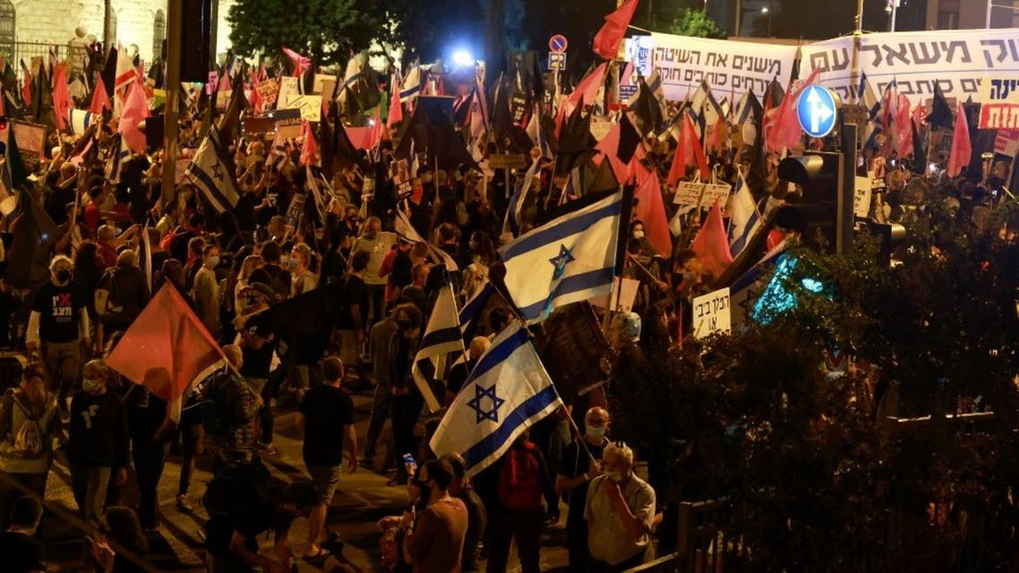Protesters wave flags during a demonstration near the residence of Israeli Prime Minister Benjamin Netanyahu in Jerusalem, on October 31, 2020, to demand his resignation over his corruption cases. (AFP)