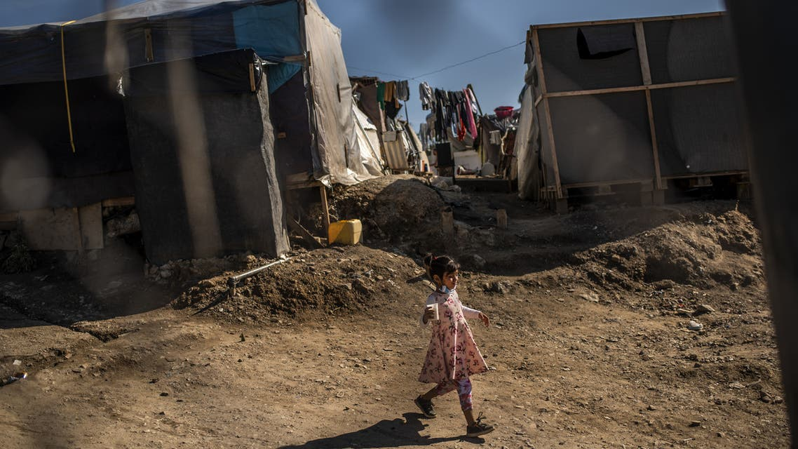 A girl walks between tents at a makeshift camp next to the Samos refugee camp, on the island of Samos on November 1, 2020. (AFP)