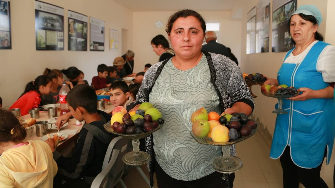 A woman holds fruit at the Armenian camp hosted by the Displacement Camp Armenian Missionary Association of America. (Supplied by the organization)