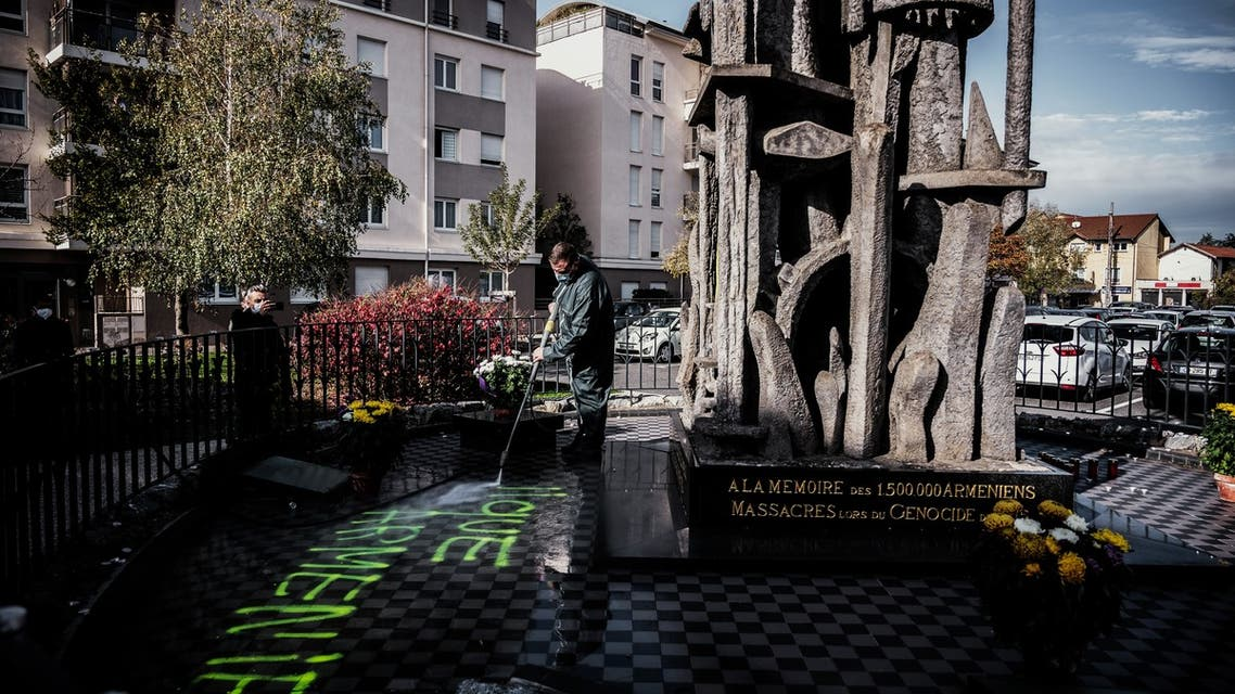 A man cleans the memorial for the Armenian genocide in Decines-Charpieu, near Lyon. (AFP)