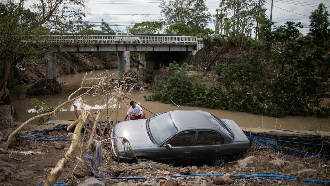 A man sits beside a car, washed away by floods caused by Typhoon Goni, in Barangay San Isidro, Batangas City, Philippines, on November 2, 2020. (Reuters)