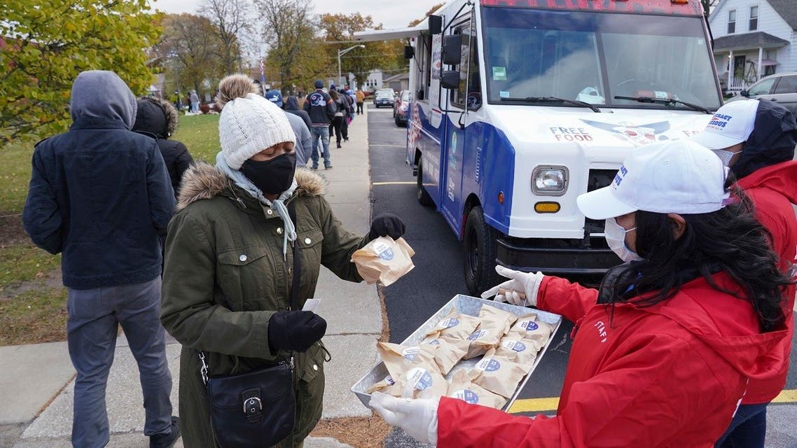 A food truck staff worker distributes free snacks as long lines form in front of the Pizza to the Polls and Uber Eats food truck, Nov. 1, 2020 in Illinois. (AP)
