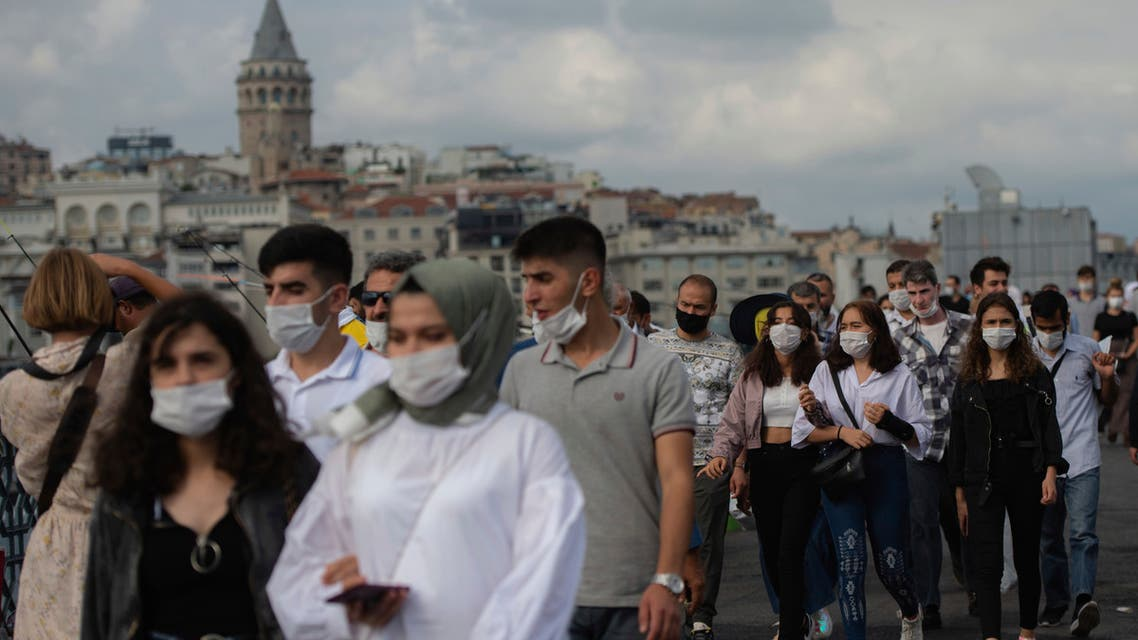 people wearing masks for protection against the spread of coronavirus, walk over Eminonu bridge in Istanbul, Friday, Sept. 11, 2020. (AP)