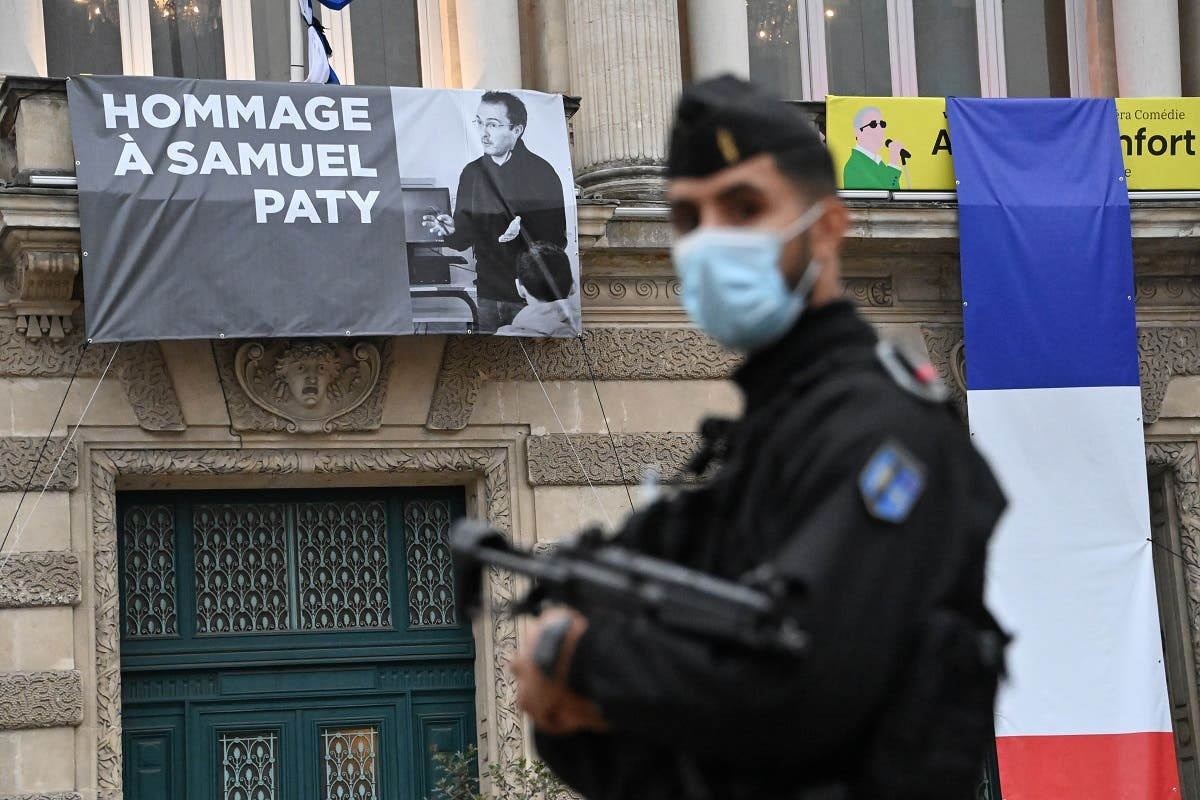 A French police officer stands next to a portrait of French teacher Samuel Paty on display on the facade of the Opera Comedie in Montpellier on October 21, 2020. (AFP)
