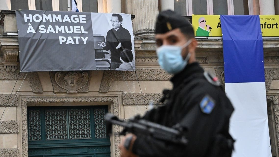 A French police officer stands next to a portrait of French teacher Samuel Paty on display on the facade of the Opera Comedie in Montpellier on October 21, 2020. (Pascal Guyot/AFP)