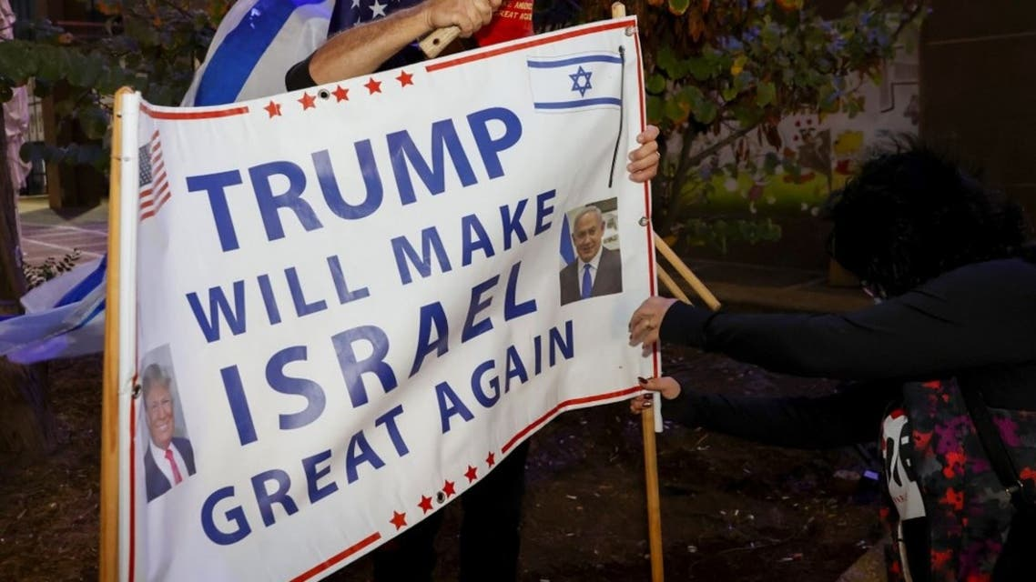 Israeli supporters of US President Donald Trump hammer a sign into the ground during a rally in the northern Israeli city of Karmiel near Haifa on November 3, 2020, to express their support for him during the US presidential election. (AFP)