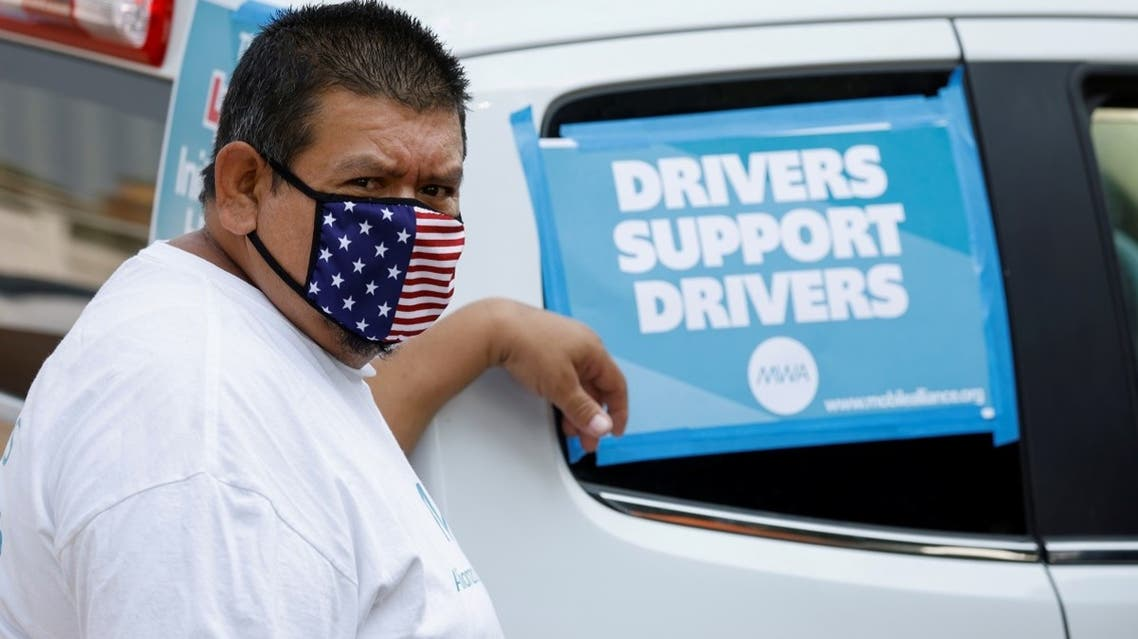 Rideshare driver Jesus Jacobo Zepeda of Lancaster, California, takes part in a rally as part of a statewide day of action to demand that ride-hailing companies Uber and Lyft follow California law and grant drivers basic employee rights'', in Los Angeles, California, US, on August 20, 2020. (Reuters)