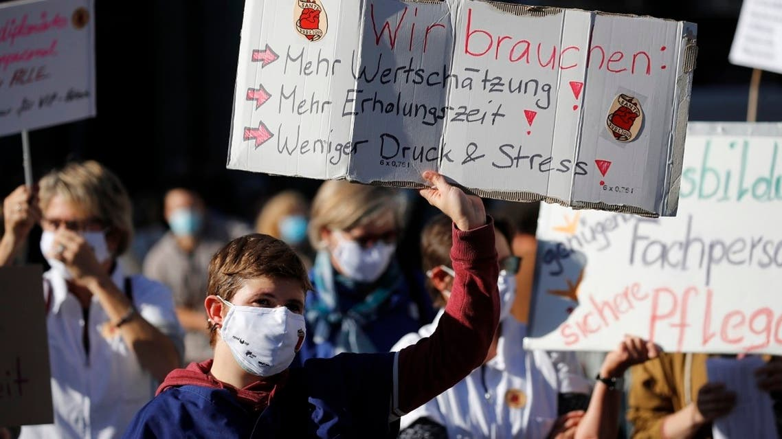 """Healthcare workers wear protective face masks as they stand with a placard """"We need: more appreciation!, more recovery time! less pressure and stress!"""" during a demonstration in Bern on October 31, 2020, as part of a week of protests to call for higher salaries and better working conditions. (AFP)"""