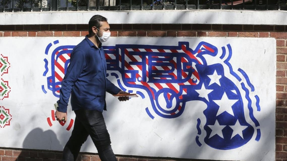 A man walks past a mural painted on the outer walls of the former US embassy in the Iranian capital Tehran, on September 29, 2020.