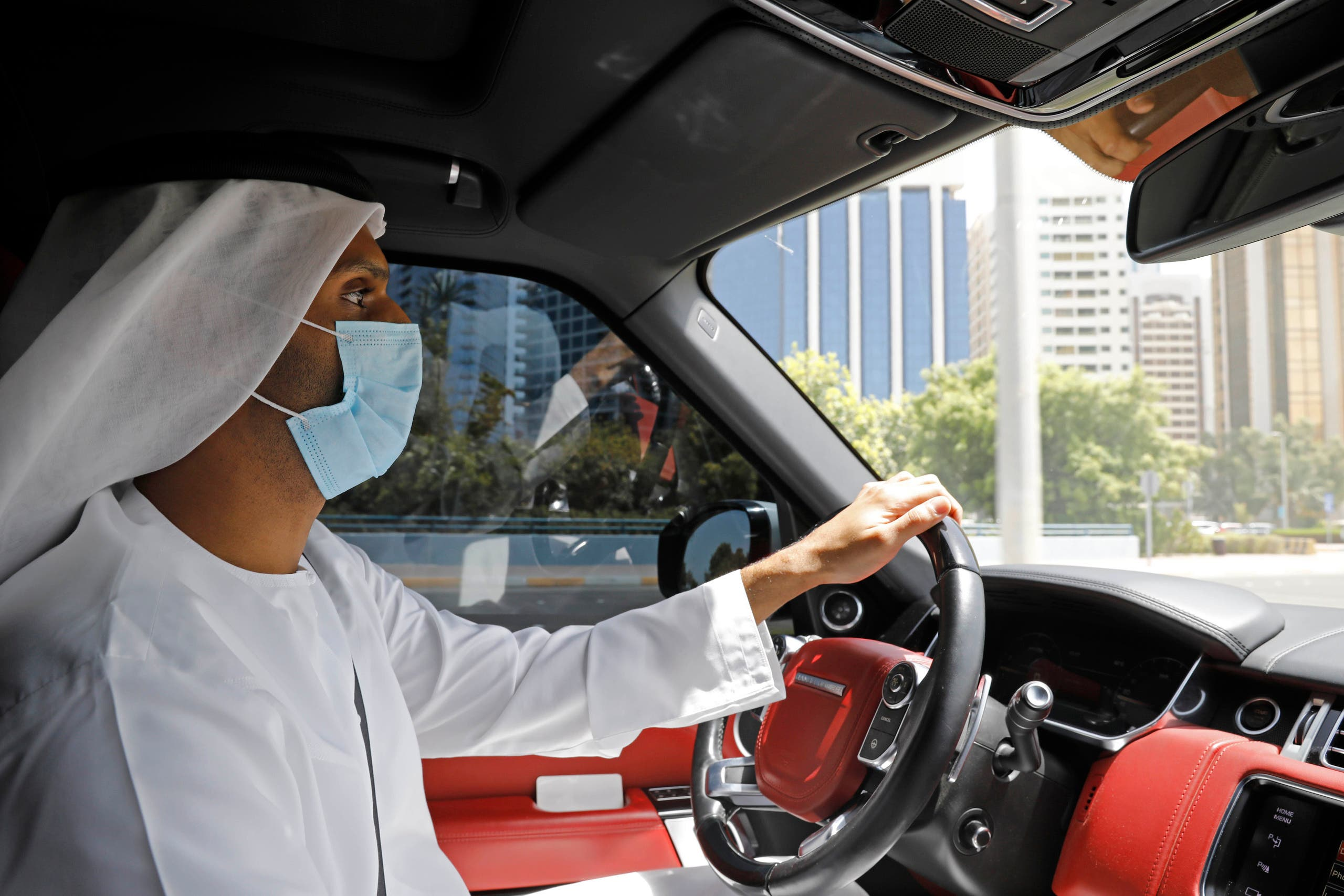 An Emirati official wears a mask as he drives a vehicle in Abu Dhabi on Sept. 1, 2020. (AP)