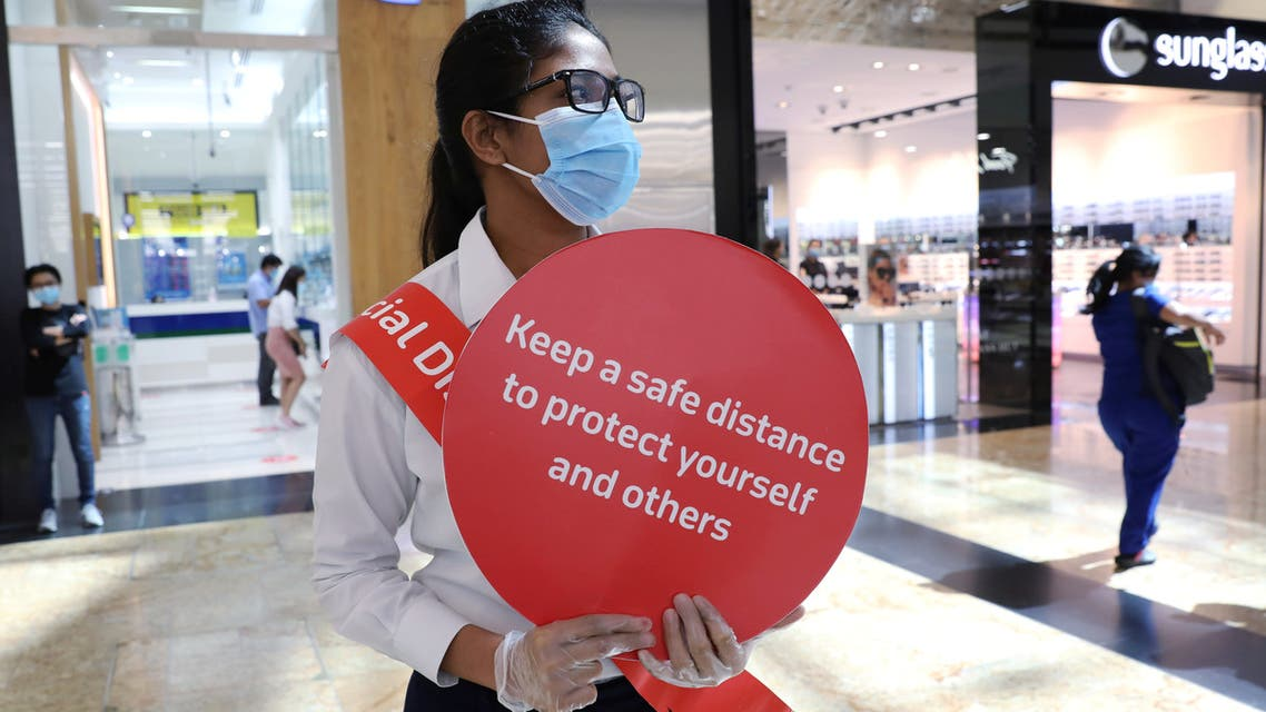 A woman wearing a protective face mask and gloves holds a sign at Mall of the Emirates after the UAE government eased a curfew and allowed stores to reopen, following the outbreak of the coronavirus disease (COVID-19) in Dubai, United Arab Emirates May 5, 2020. (AP)