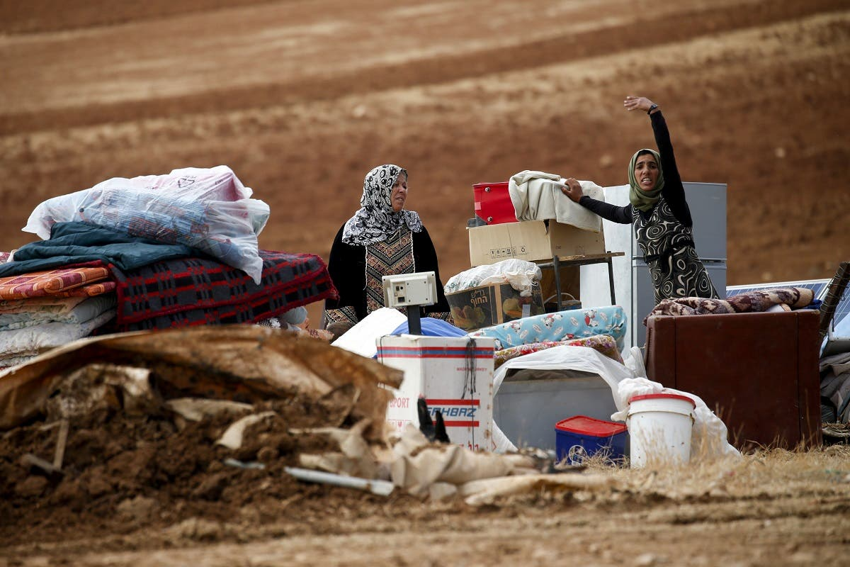 Palestinian Bedouins stand next to their belongings after Israeli soldiers demolished their tents in an area east of the village of Tubas, in the occupied West Bank, on November 3, 2020. (Jaafar Ashtiyeh/AFP)