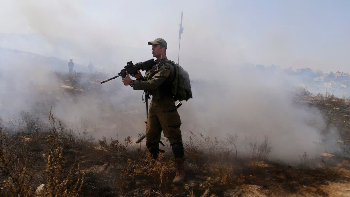 File photo of an Israeli soldier pointing his weapon towards a Palestinian demonstrator during clashes in Asira al-Qibliya near the West Bank city of Nablus on Sept. 18, 2020. (AP)