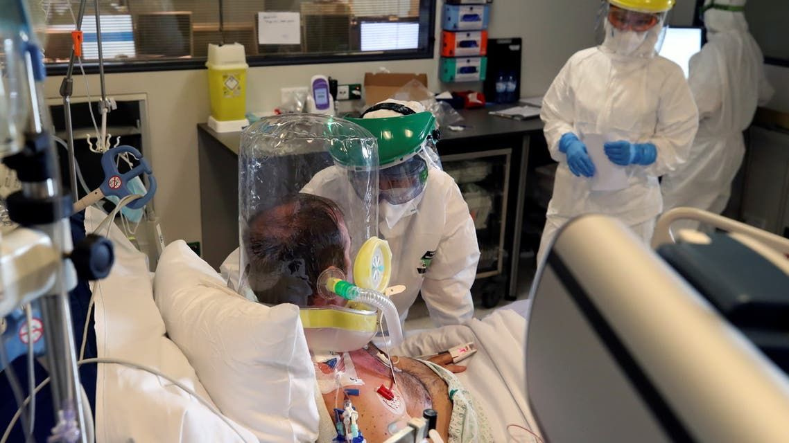 Members of the medical personnel wearing full protective suits treat a patient infected with the coronavirus disease (COVID-19), who is wearing a full covering oxygen mask, in the intensive care unit at the CHU de Charleroi hospital, in Charleroi, Belgium, November 5, 2020. REUTERS/Yves Herman