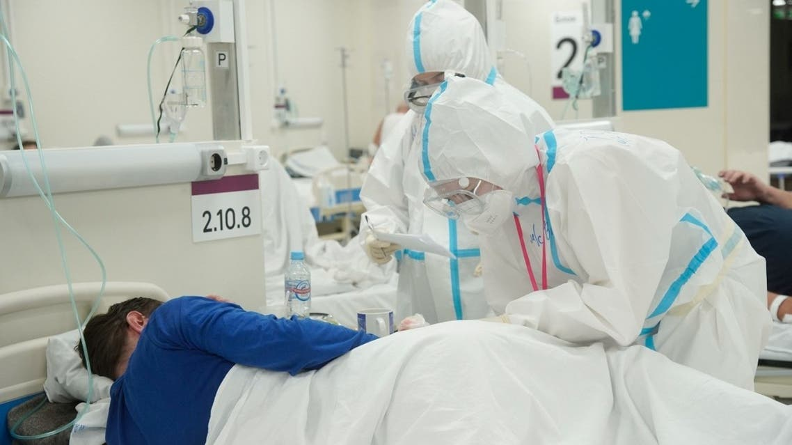 Medical specialists wearing personal protective equipment (PPE) take care of a patient at a temporary hospital set up, amid the outbreak of the coronavirus disease (COVID-19) in Moscow, Russia. (Reuters)