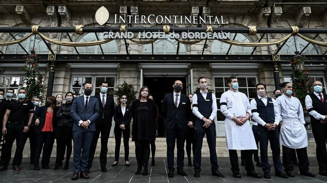 French workers wearing black armbands stand ouside the Intercontinental hotel in Bordeaux, south-western France on October 2, 2020. (AFP)