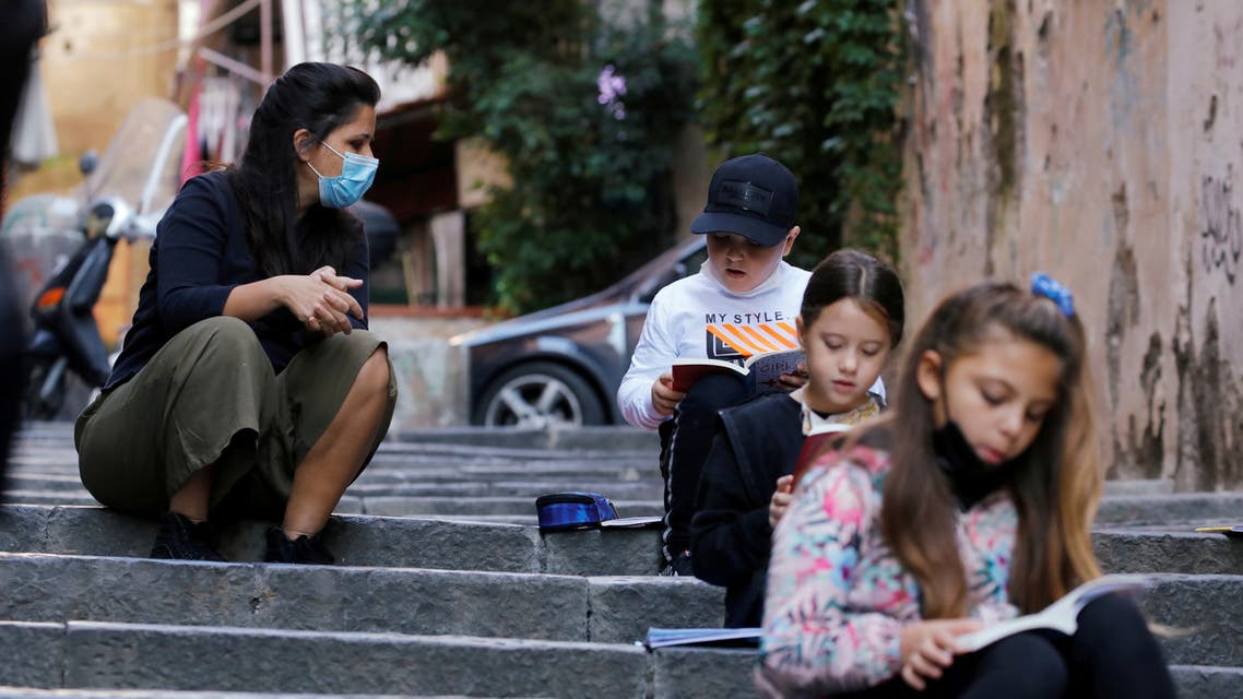 FILE PHOTO: Naples school teacher Pamela Buda holds her lessons to her social distancing students on public steps, after the region of Campania closed schools due to a spread of the coronavirus disease (COVID-19) in Naples, Italy, October 21, 2020. REUTERS/Ciro De Luca/File Photo