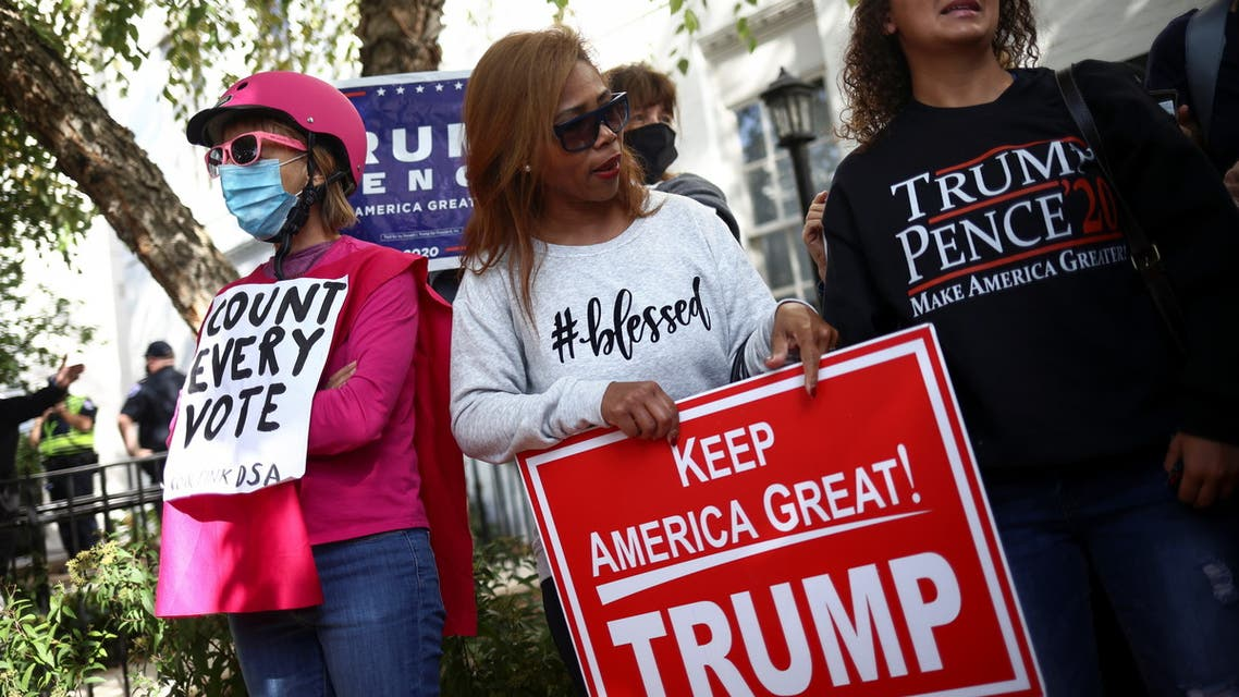 A counter protester stands next to supporters of U.S. President Donald Trump as they demonstrate near the Republican National Committee building after Election Day, in Washington, D.C., U.S., November 5, 2020. REUTERS/Hannah McKay