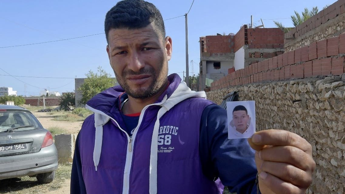 Yasin, the brother of the Nice assailant Brahim Aouissaoui, shows his picture in front of the family home in the Tunisian city of Sfax, on October 30. (AFP)