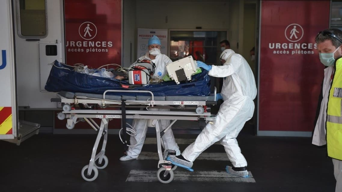 Medical staff carry a patient infected with the Covid-19 disease into Strabourg hospital's emergency unit following his arrival by plane from the Lyon's area on November 6, 2020 in Strasbourg, eastern France. (AFP)
