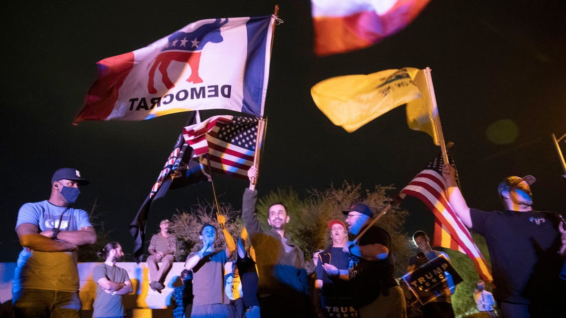 Man flies a Democratic Party flag amidst a group of U.S. President Donald Trump supporters during a Stop the Steal protest at Clark County Election Center in North Las Vegas, Nevada, U.S. November 5, 2020. REUTERS/Steve Marcus