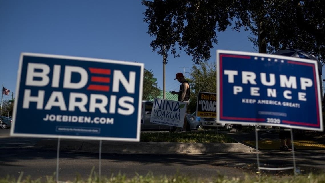 Biden and Trump campaign signs are displayed as voters line-up to cast their ballots during early voting at the Alafaya Branch Library in Orlando, Florida, on October 30, 2020. (AFP)