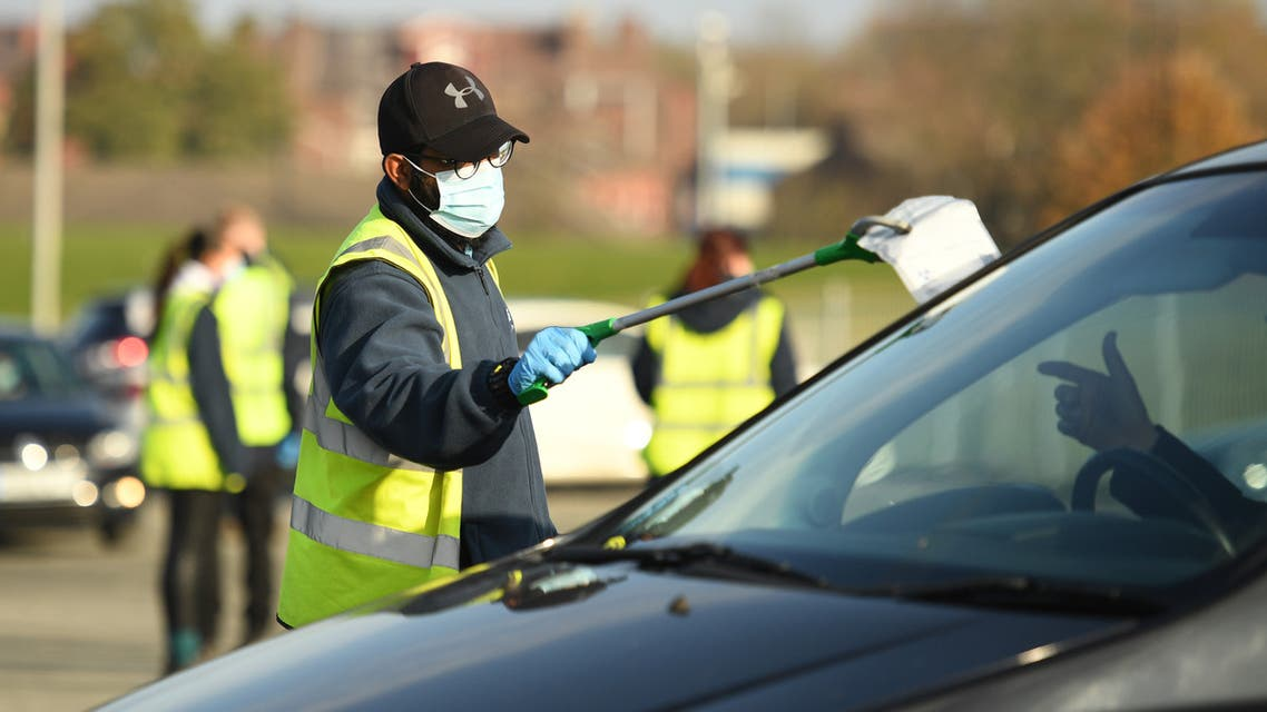 A worker speaks to a member of the public arriving by car at the long-established testing facility for the novel coronavirus COVID-19 in Liverpool. (AFP)