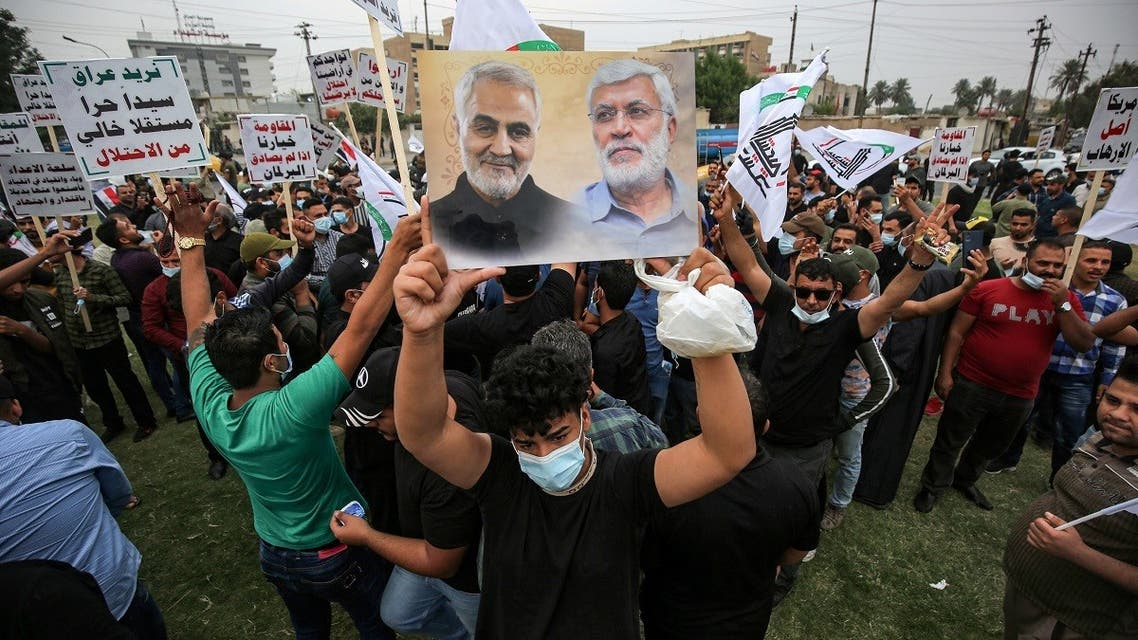 A supporter of the Iran-backed Hashed al-Shaabi (Popular Mobilization) paramilitary forces stands holding a picture showing the faces of (L to R) Qassem Soleimani and Abu Mahdi Al-Muhandes during a rally outside the entrance to Baghdad's highly-fortified Green Zone on November 7, 2020, demanding the departure of remaining US forces from Iraq. (Ahmad Al-Rubaye/AFP)