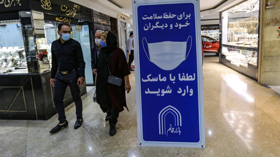 Iranians walk next to a sign advising people to wear masks on their way to shop in Tajrish square in the capital Tehran on November 1, 2020, amid the novel coronavirus pandemic crisis. Iran yesterday announced the expansion beyond Tehran of measures against Covid-19, amid growing calls for a full lockdown after the country posted a string of record highs in deaths and infections.